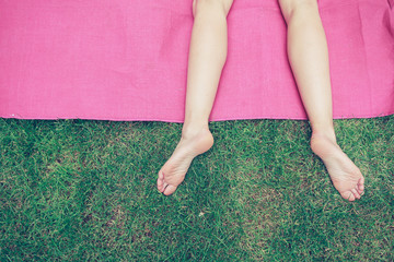 The legs of a young woman on the grass