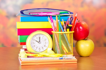 Alarm clock, set of school accessories and apples