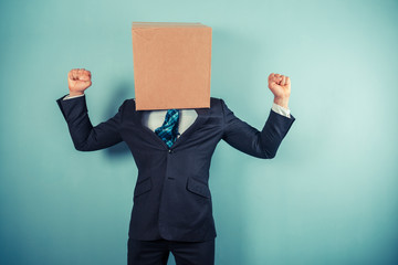 Triumphant businessman with box on head
