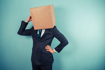 Businessman with a box on his head is cofused