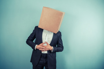 Businessman with box on head has stomach pains