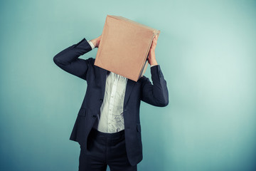 Businessman with box on head has a headache
