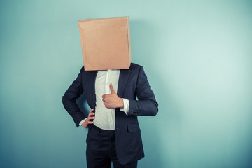 Businessman with box on his head giving thumb up