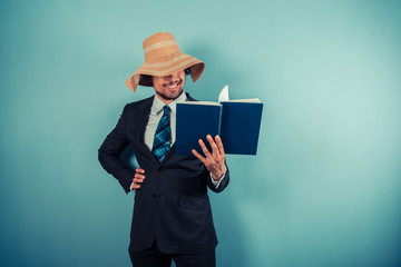 Businessman wearing beach hat is reading