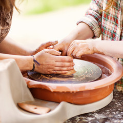 Female Potter creating a bowl on a Potters wheel, the master pot
