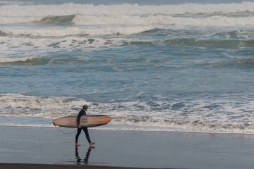 surfer on Muriwai beach, New Zealand