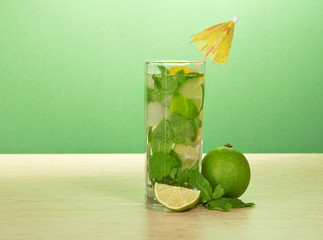 Mojito glass, an umbrella, leaf of mint and lime