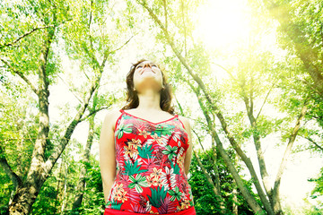 Young woman in sun dress walking through spring forest