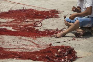 Fisherman repairs his net