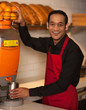 Cheerful chef making fresh orange juice