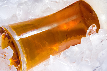 Glass of cold beer lying in the ice