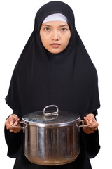 Muslim woman carries a large pot