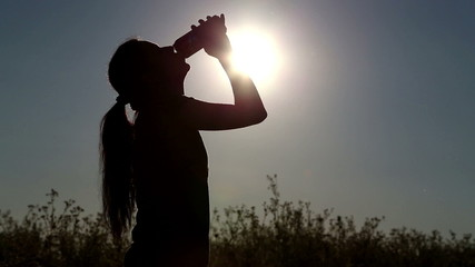 Girl drinks water from a bottle (banks)