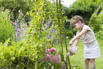 Petite Fille avec un arrosoir dans un jardin
