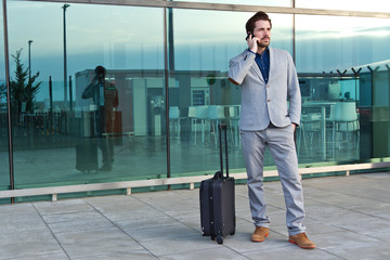 Urban business man talking on smart phone outside in airport