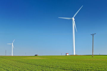 Windmill turbine on blue sky. Wind energy. Modern green power.