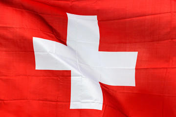 Swiss flag in the wind in sunlight