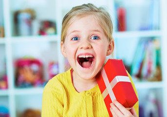 Happy little girl hold red gift.
