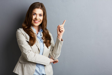 Portrait of smiling business woman pointing finger