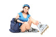 Schoolgirl with roller skates sitting on the ground
