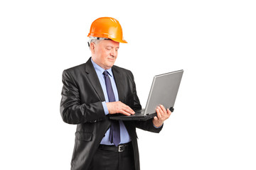 Mature construction worker working on a laptop