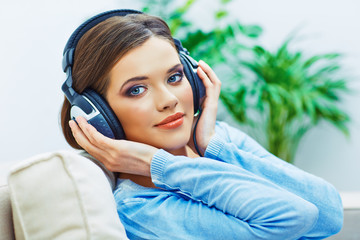 Beautiful girl face portrait with listening music in headphones
