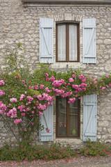 Fenster, Fensterläden und Rosen an Bruchsteinhaus