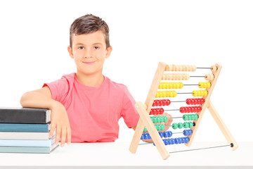 Boy sitting at a desk with an abacus and books on it