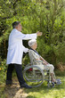 senior patient in wheelchair with  friendly caregiver