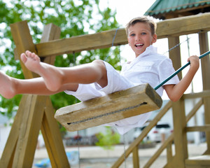Happy boy having fun on a swing in a summer park.