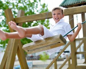 Happy boy having fun on a swing in a summer park.