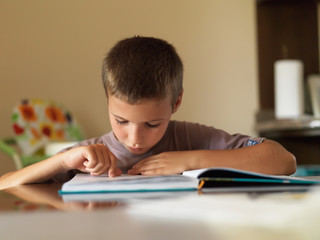 Boy reading a book while sitting at table at home.