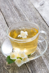 cup of green tea with jasmine on wooden background