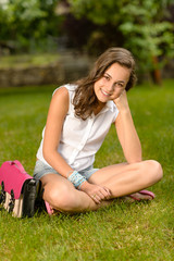 Smiling teenage girl sitting grass with satchel