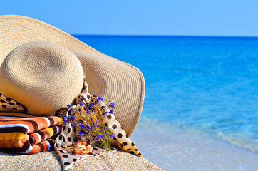 Woman beach hat, bright towel and flowers against blue ocean