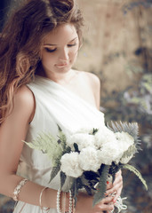 Bride portrait. Girl with wedding bouquet of white flowers, soft