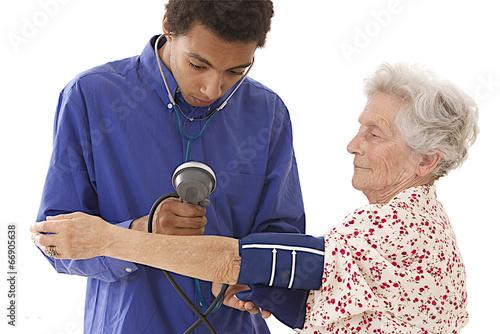 jeune docteur prise de  pression arterielle dune personne agée