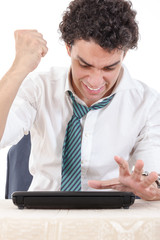 male frustrated with work sitting in front of laptop with his ha