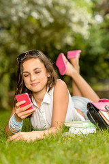 Teenage girl with mobile phone lying grass