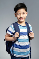 Little Asian child standing with a kit bag slung over his should