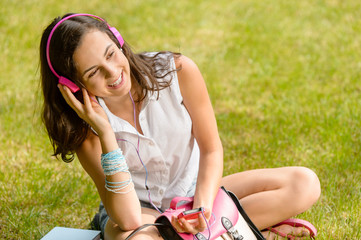 Summer student girl listen music sitting grass