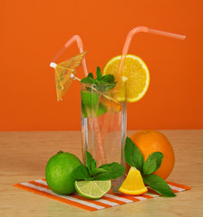 Glass with drink, ripe orange and lime