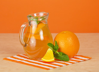 Jug with drink, ripe oranges, a striped napkin