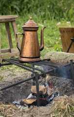 copper teapot on campfire
