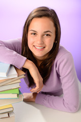 Smiling student girl with pile of books