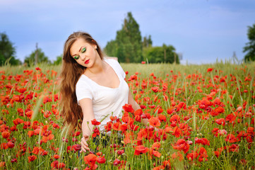 Young beautiful girl in a poppy field