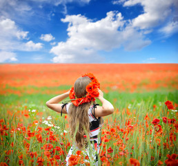 Beautiful young woman in red bright poppy field
