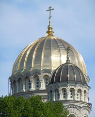 Gilded dome of orthodox church with three-barred cross
