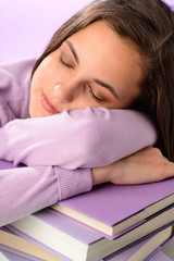 Tired student girl sleeping on purple books