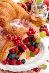Fresh croissants with fruits.